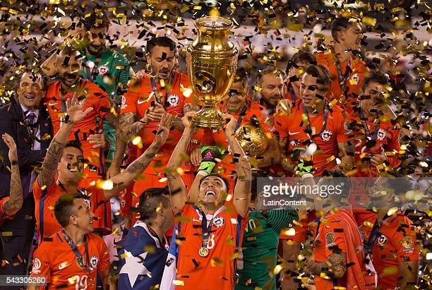 Gonzalo Jara of Chile holds up the Copa America Centenario Trophy with his teammates around him following the championship match between Argentina...
