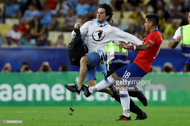 Gonzalo Jara of Chile throws a kick to a pitch invader during the Copa America Brazil 2019 group C match between Chile and Uruguay at Maracana...