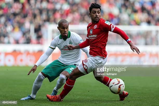 Gonzalo Jara of Mainz is challenged by Theodor Gebre Selassie of Bremen during the Bundesliga match between 1 FSV Mainz 05 and Werder Bremen at...