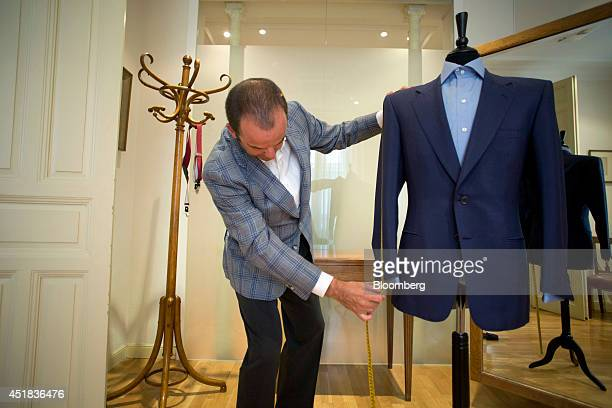 Gonzalo Lopez Larrainzar a bespoke tailor measures a handmade men's jacket displayed on a mannequin at his luxury outfitters in Madrid Spain on...