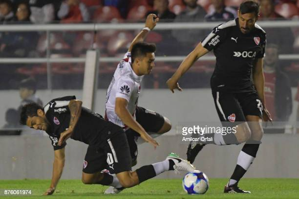 Gonzalo Martinez of River Plate fights for the ball with Walter Erviti and Jonas Gutierrez of Independiente during a match between Independiente and...