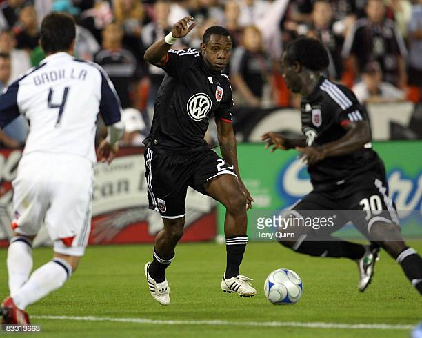 Gonzalo Martinez passes the ball through to Francis Doe of DC United as Gabriel Badilla of New England Revolution closes in during an MLS match at...