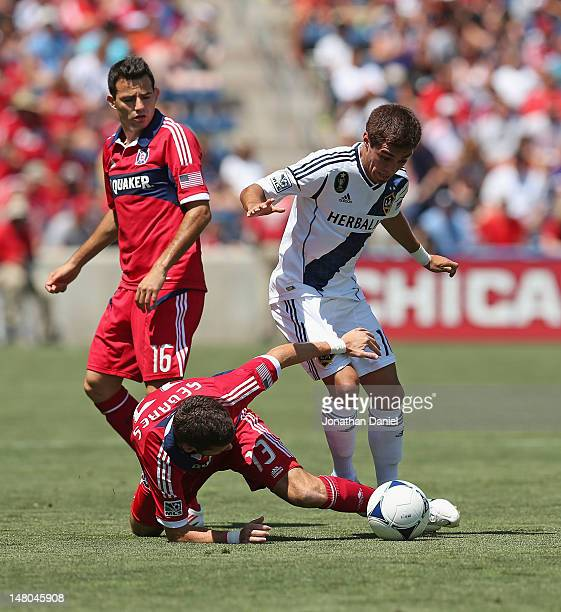 Gonzalo Segares of the Chicago Fire tries to kick the ball away after falling next to Hector Jimenez of the Los Angeles Galaxy as Marco Pappa watches...
