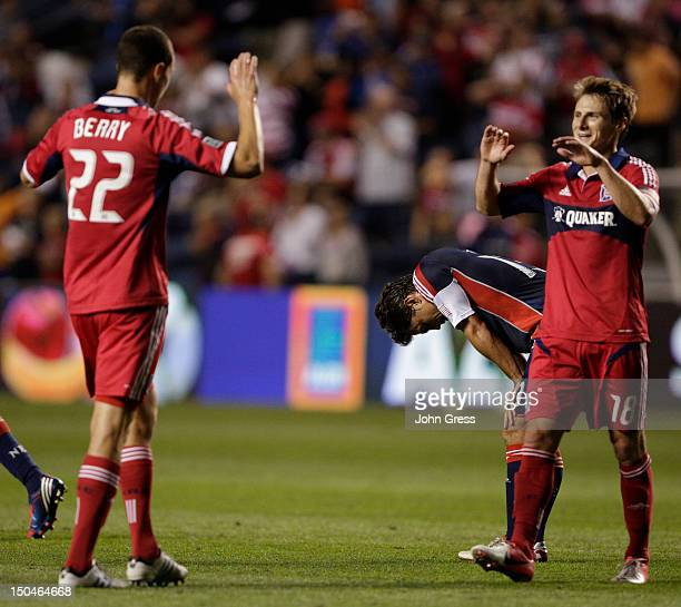 Gonzalo Segares of the New England Revolution reacts to losing to the Chicago fire 21 as Chris Rolfe and Austin Berry of the Chicago Fire celebrate...