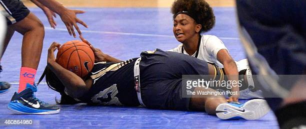 Good Counsel's Nicole Enabosi looks to pass to a teammate as she goes to the floor with Roosevelt's Octavia Wilson at her feet in the Title IX...