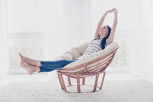 Good day! Happy cute pretty woman lying in the armchair on the weekend and stretching 941847258