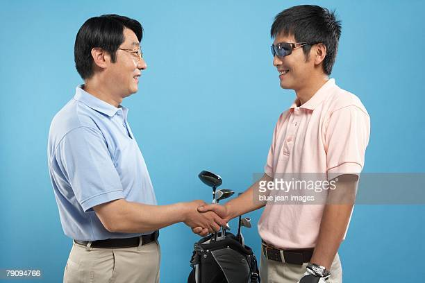 Good game. Two golfers shaking hands.