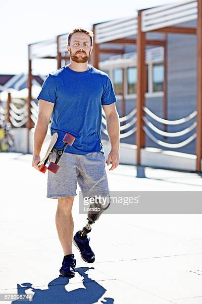 Good looking casual skateboarder male walking at summer beach location