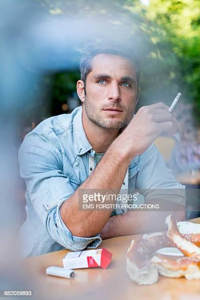 good looking man is vaping in the beergarden