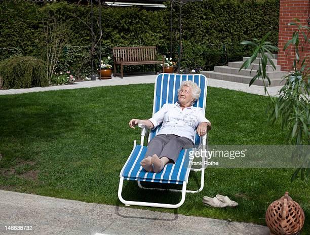 good looking old lady enjoys the sun in the garden - アウトドアチェア ストックフォトと画像