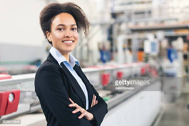Good looking self-confident businesswoman smiling at the factory