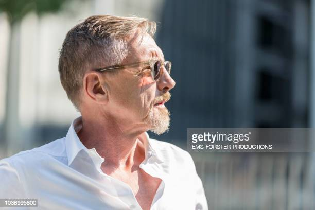 good looking senior man in his early 60s in good shape with white shirt and sunglasses outside in bright sunlight. - einzelner mann über 40 stock-fotos und bilder