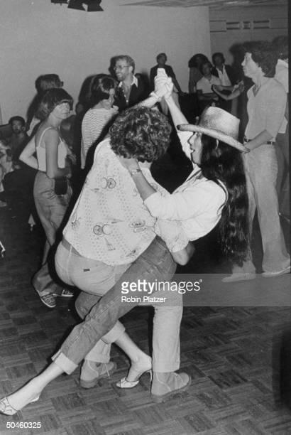 Good of singer/actress Cher Bono dancing w unidentified man at Studio 54