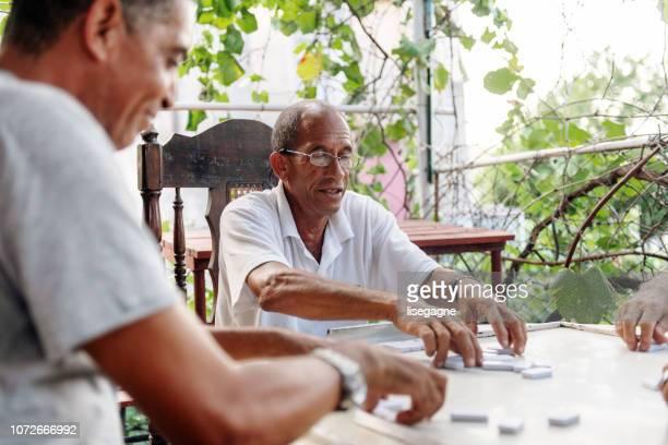 good old latino friends playing dominos - tempo turno sportivo foto e immagini stock