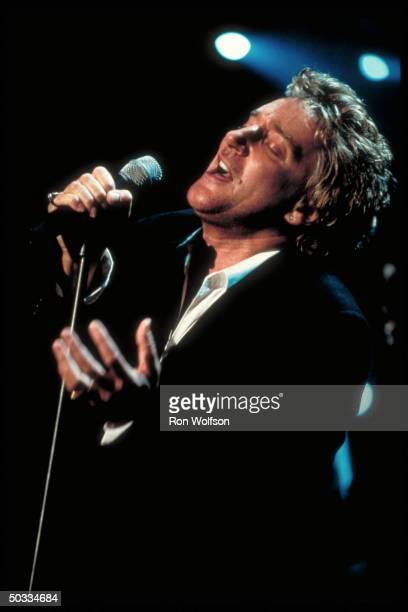 Good portrait of rock star Rod Stewart singing into microphone
