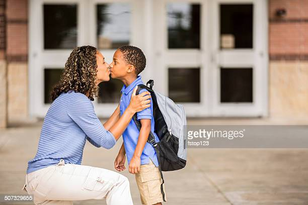 Auf Wiedersehen.  Kleinen Sohn küsst Mutter am ersten Schultag.