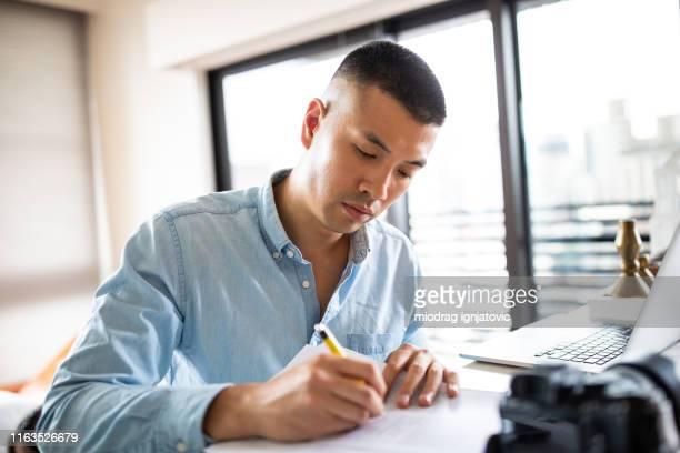 goed uitziende chinese man ondertekenen papieren documenten - ondertekenen schrijven stockfoto's en -beelden
