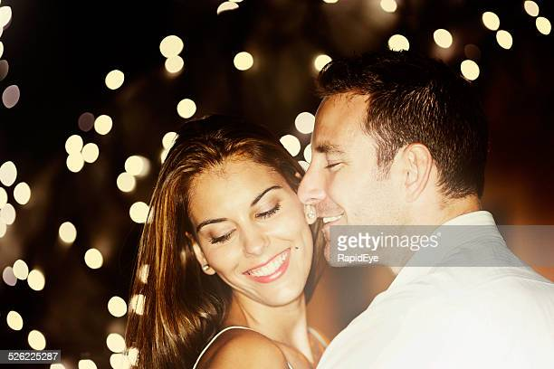 Good-looking couple embrace, smiling, under twinkling lights