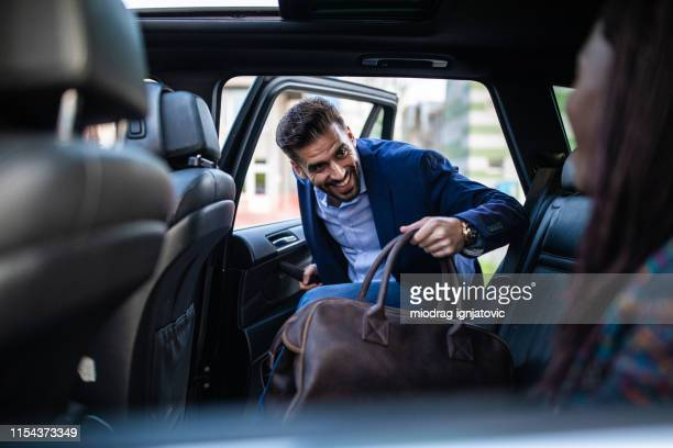good-looking man entering ride sharing car - entrar imagens e fotografias de stock