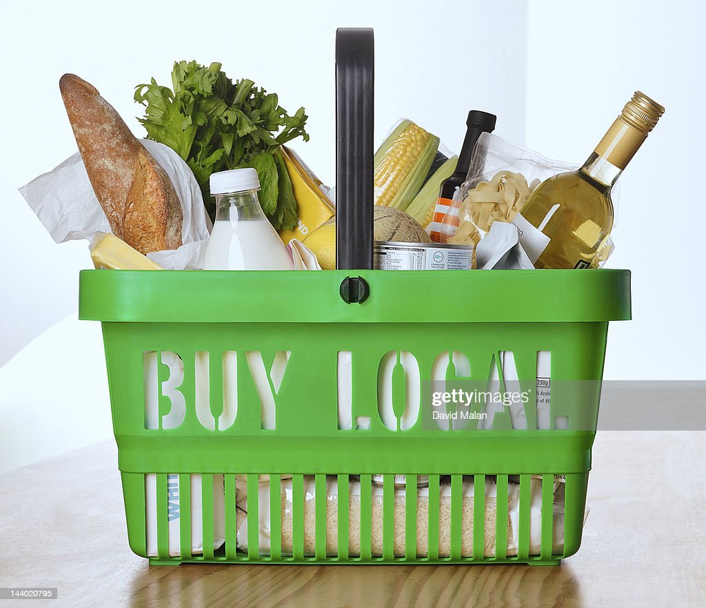 Goods in a shopping basket with 'buy local' on it : Stock Photo