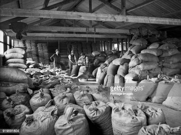 Goods shed Ulverston Goods Station Cumbria 1927 Men moving sacks of dairy meal in a depot used by the Furness and South Cumberland Supply Association...
