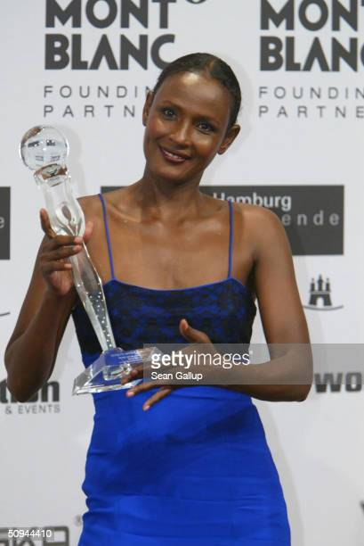 Goodwill Ambassador and former model Waris Dirie holds her World Fashion Icon Award at the Women's World Award at Congress Center June 9 2004 in...