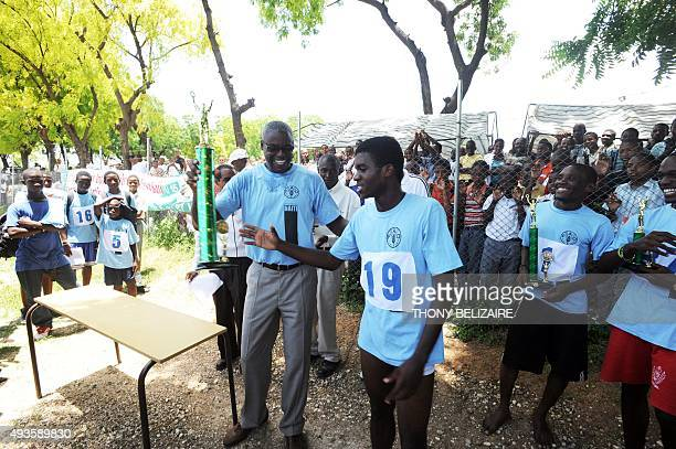 FAO Goodwill Ambassador and Olympic track legend Carl Lewis awards student with a cup after his participation in the competition to the 'Course...