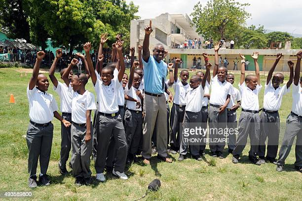 FAO Goodwill Ambassador and Olympic track legend Carl Lewis meets group of students of 'St Louis de Gonzague' school in PortauPrince during his...