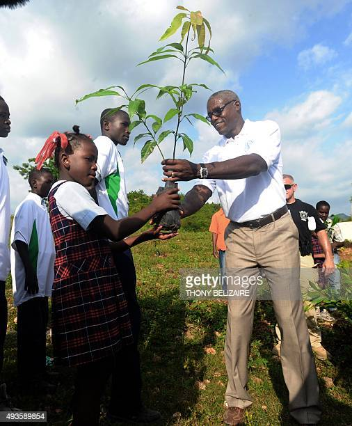 FAO Goodwill Ambassador and Olympic track legend Carl Lewis planting trees with school children in Leogane on June 14 2011 during his twoday visit to...