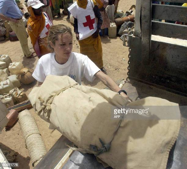 UNHCR goodwill ambassador Angelina Jolie helps Sudanese refugees load their belongings onto a truck near Tine 04 June 2004 The refugees are crossing...