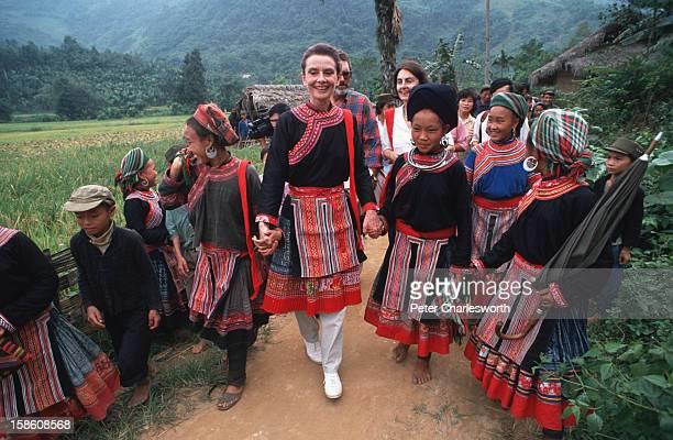 "Goodwill Ambassador, Audrey Hepburn, walks down a village pathway with Vietnamese ""Dao"" hill tribe children. She is wearing an ethnic minority..."