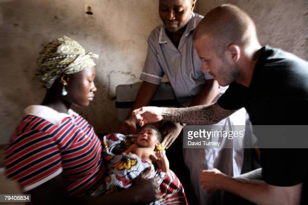 Goodwill Ambassador David Beckham administers a dose of oral polio vaccine to twodayold Mariatsu as he joins nurse Angela on a visit to the mother's...