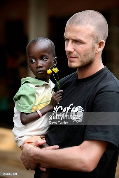Goodwill Ambassador David Beckham carries fiveyearold Foday during a tour of a therapeutic feeding center on January 19 2008 in Makeni Sierra Leone...