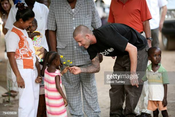 Goodwill Ambassador David Beckham is greeted by fiveyearold Senyo who suffers from malnutrition with yellow flowers upon his arrival at a therapeutic...