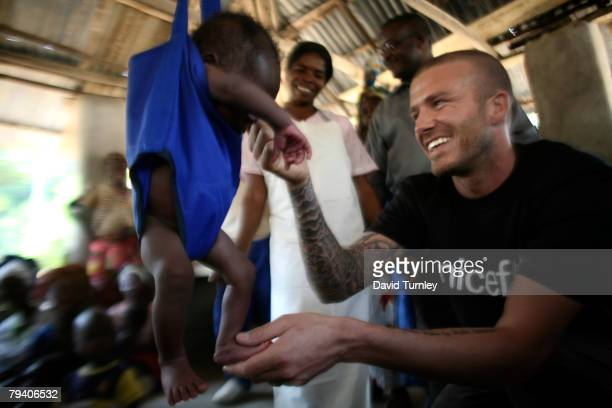 Goodwill Ambassador David Beckham plays with 19dayold Momoh who is being weighed in a sling scale at a UNICEFsupported community health outreach post...