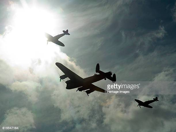 Goodwood Revival Meeting Lancaster bomber and 2 Spitfires in aerial display Artist Unknown