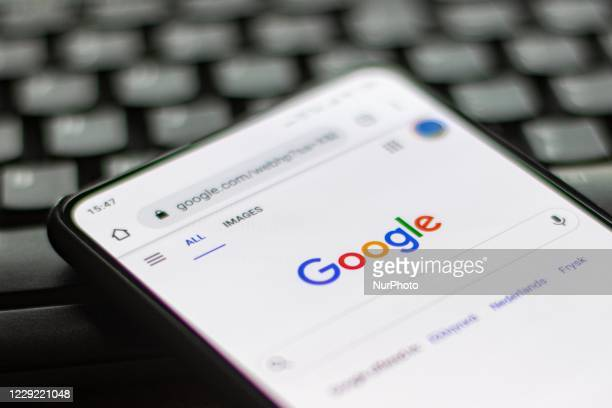 Google closeup logo displayed on a phone screen, smartphone on a keyboard is seen in this multiple exposure illustration, the company's symbol is...