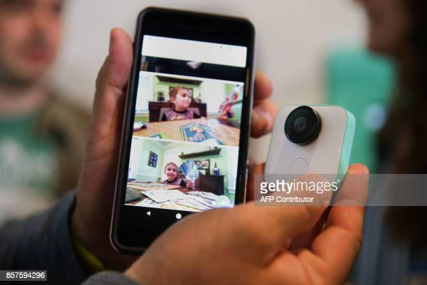A Google employee holds up the new Pixel 2 smartphone and Google Clips wireless camera at a product launch event on October 4 2017 at the SFJAZZ...