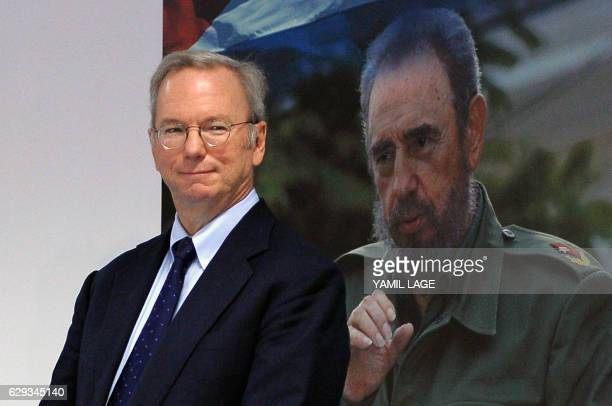 Google Executive Chairman Eric Schmidt poses beside a picture of late Cuban political leader Fidel Castro during the signing of a bilateral agreement...
