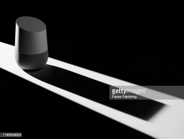 Google Home smart speaker casting a sinister shadow, to represent issues of privacy and security, taken on December 12, 2019.