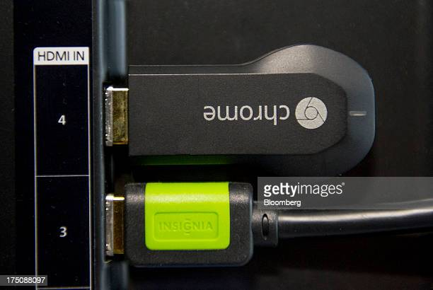 A Google Inc Chromecast internet television dongle is displayed in the HDMI port of a television in San Francisco California US on Tuesday July 30...