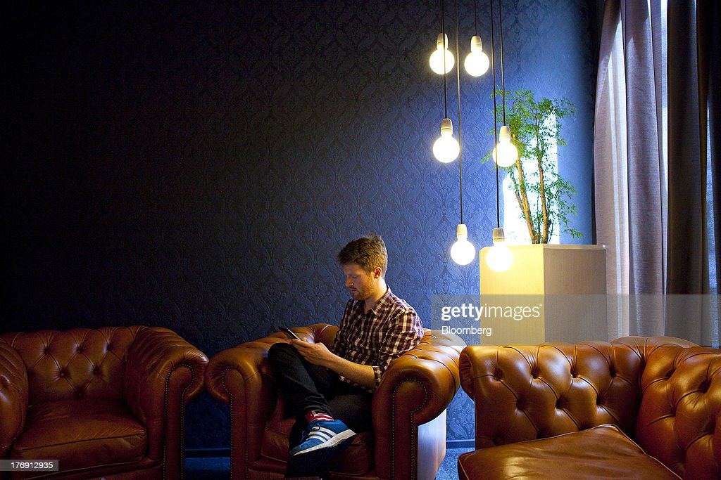 A Google Inc. employee uses a personal mobile device as he sits in a leather armchair inside the company's offices in Berlin, Germany, on Friday, Aug. 16, 2013. Google, based in Mountain View, California, is seeking to revive Motorola Mobility's smartphone business, recently announcing a new flagship Moto X smartphone with customizable colors that will be assembled in the U.S. Photographer: Krisztian Bocsi/Bloomberg via Getty Images