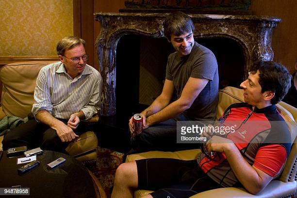 Google Inc executives from left Eric Schmidt chairman and chief executive officer and cofounders Larry Page and Sergey Brin speak with members of the...