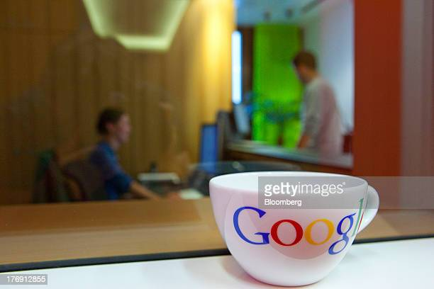A Google Inc logo sits on a coffee cup as employees work inside the company's offices in Berlin Germany on Friday Aug 16 2013 Google based in...