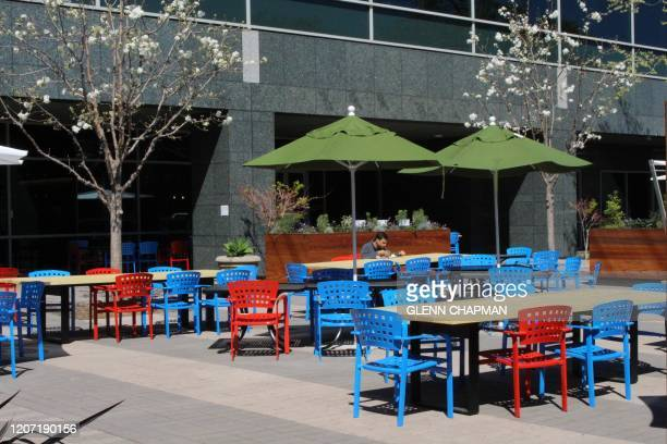 """Googler"""" eats alone in the sun at lunch time on March 12, 2020 at the internet company's main campus in the Silicon Valley city of Mountain View,..."""