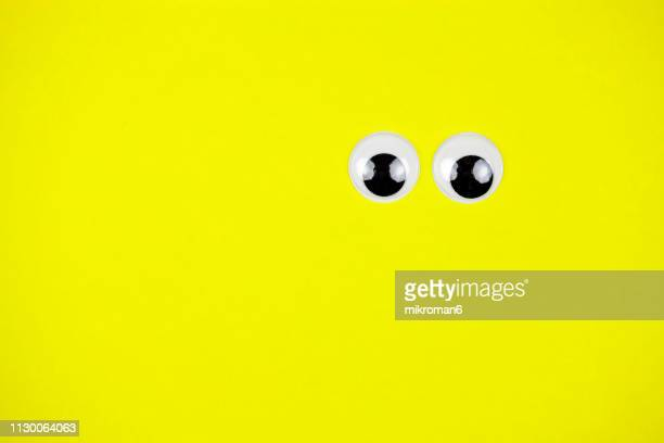 googly eyes looking up on colored background - animation stock pictures, royalty-free photos & images
