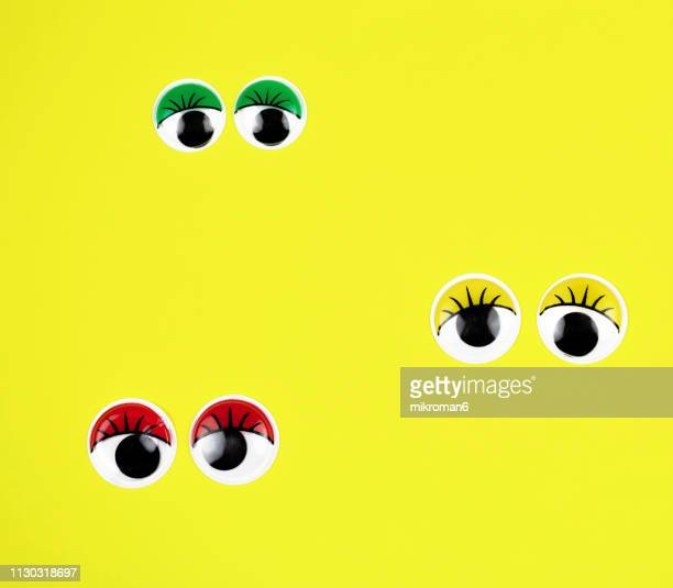 googly eyes looking up on colored background - googly eyes stock pictures, royalty-free photos & images