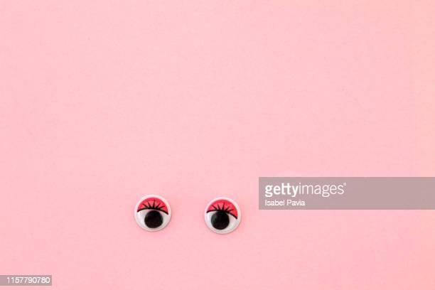 googly eyes looking up on pink background - googly eyes stock pictures, royalty-free photos & images
