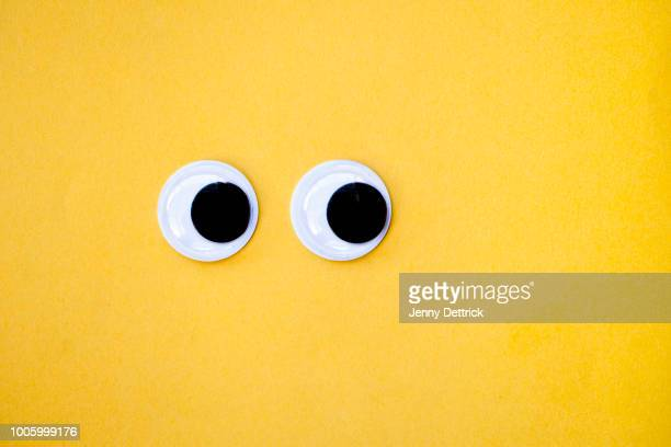 googly eyes on yellow - arti e mestieri foto e immagini stock
