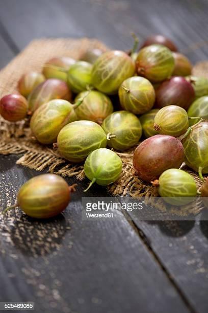 Gooseberries, Ribes uva-crispa, on jute and dark wooden table